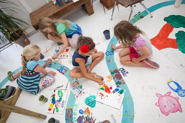 Kids creating floor art at Marvegos exhibit